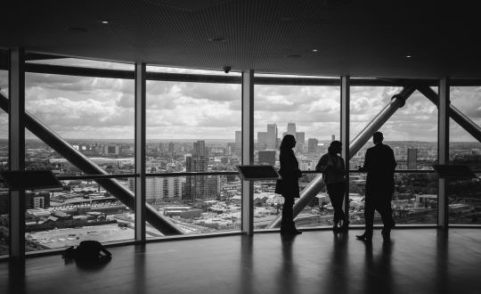 black-and-white-image-of-colleagues-standing-in-office-and-looking-at-city-view-through-window